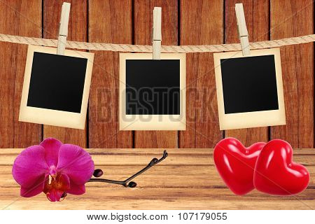 Photo Cards Hanging On Rope On Clothespins, Orchid And Two Red Hearts Over Wooden Background