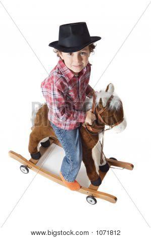Adorable Kid Riding A Toy Horse