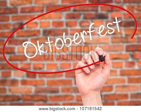Man Hand writing Oktoberfest with black marker on visual screen.