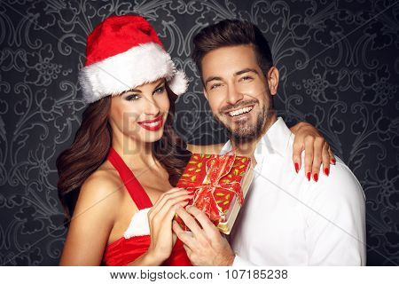 Young Couple Holding Gift At Christmas