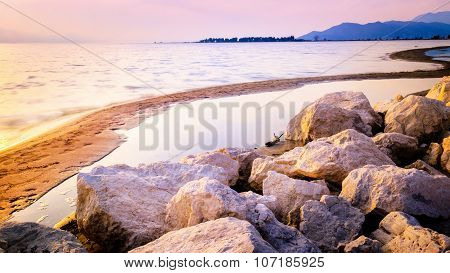 Warm Sunset On The Sand Beach With Rocks In Front In Southern Croatia
