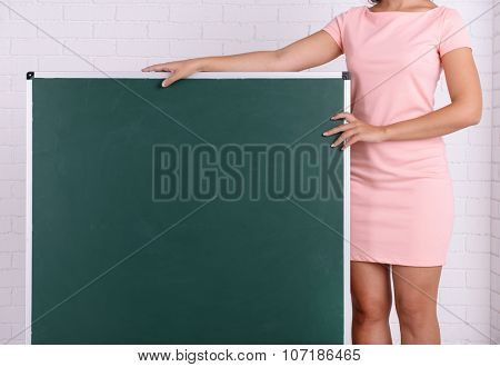 Woman in rosy dress with green blackboard against a brick wall, close up