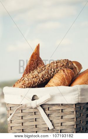 Various kinds of fresh tasty bread in wicker basket. Shallow depth of field, vintage style.