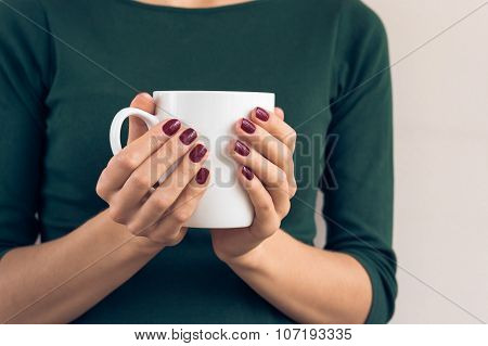Woman In A Green T-shirt And A Maroon Manicure Holding White Cup