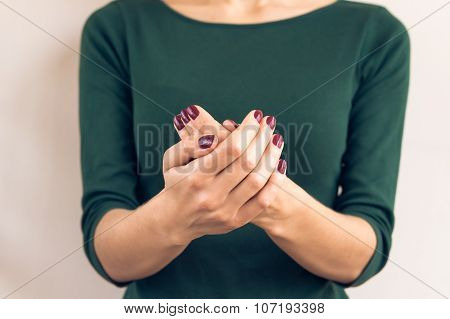 Woman In Green T-shirt Shows A Hands With A Maroon Manicure