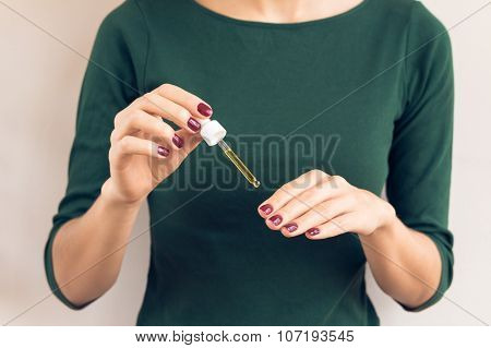 Woman In Green T-shirt And Maroon Manicure Applying Oil For Nails From The Pipette