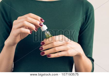Woman In A Green T-shirt And A Maroon Manicure Holding A Jar With A Cosmetic Oil