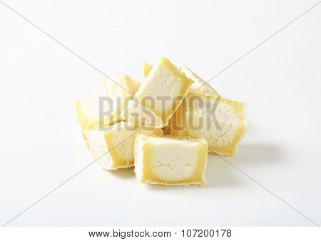 handful of sliced soft white rind cheese on white background