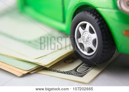 Green toy car on the dollars