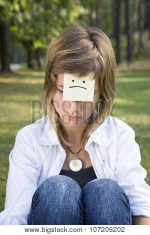 Sad Girl Sits On Green Grass In Forest. On The Forehead Shows (drawn) Sad Icon.
