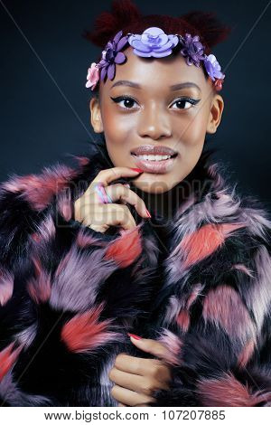 young pretty african american woman in spotted fur coat and flowers jewelry on head