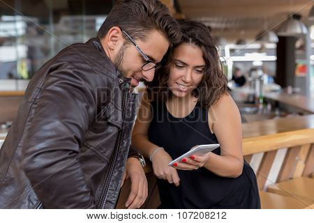 Male And Female Staring At Smartphone