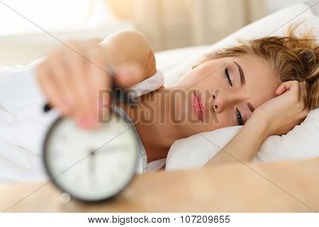 Sleepy Young Woman Trying Kill Alarm Clock