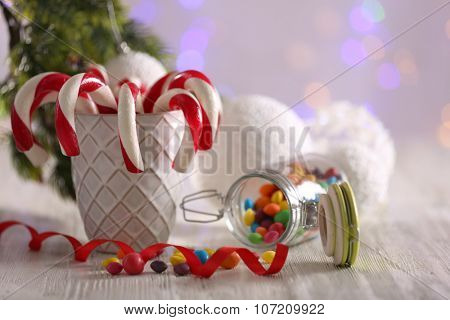 Christmas Candy Canes in cup on table on light background