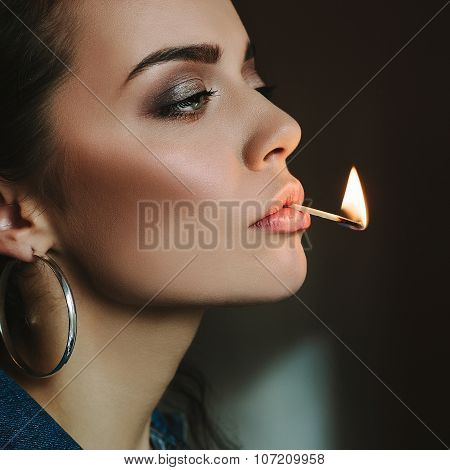 Woman With Perfect Skin Holding Her Lips With A Match Flame