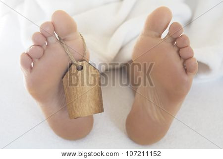 Naked Feet  In Bed With Wooden Tag