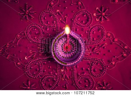 Beautiful decorative Diwali lamp on embellished purple background. Happy Diwali Greeting Card.
