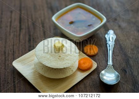 Hot idlis with dollop of butter on top and tangy sambar. An Indian regional cuisine.