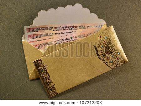 One thousand rupee notes in a decorative golden envelopes.