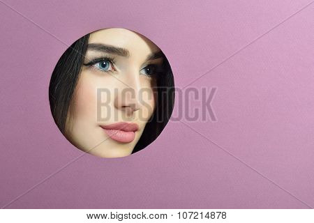 Beauty female port?ait. Young beautiful woman look out of circle in purple paper. Girl's face in round paper frame with copyspace for your message