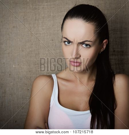 Portrait of angry, dissatisfied young woman knits her brows over canvas background, image toned.
