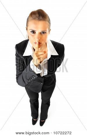 Full length portrait of modern business woman with finger at mouth. shh gesture