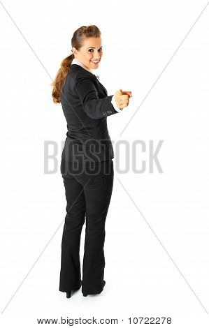 Full length portrait of friendly modern business woman pointing finger at you