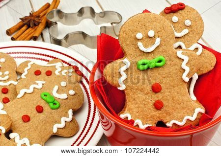 Christmas gingerbread men cookies in red bowl on white wood