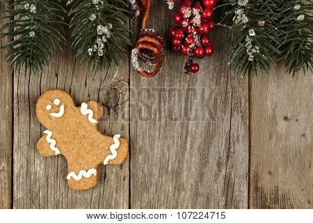 Gingerbread man on rustic wood with tree branch border