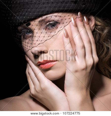 Beautiful woman in black hat with veil
