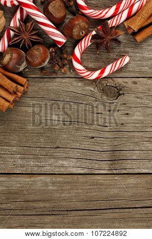 Border of Christmas baking goods and candies against rustic wood