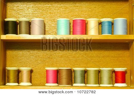 Colorful Spool Of Thread On Wood Shelf