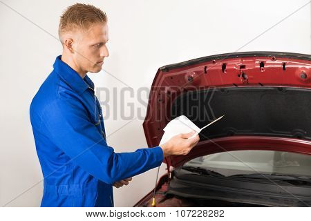 Mechanic Checking Oil Level In Car Engine
