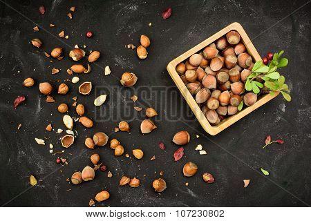 Hazelnuts In Nutshell In A Wooden Box Grunge Dark Backdrop. Top View.