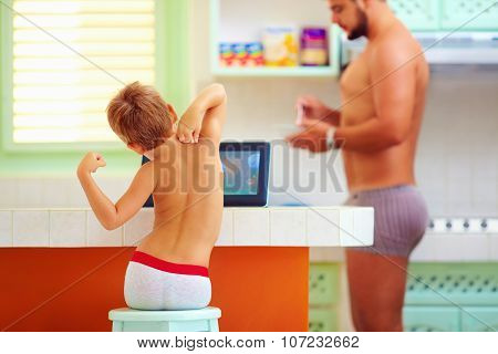 Father And Son In The Morning At Their Daily Chores In The Kitchen
