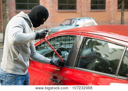 Thief With Mask Opening Car's Door By Crowbar