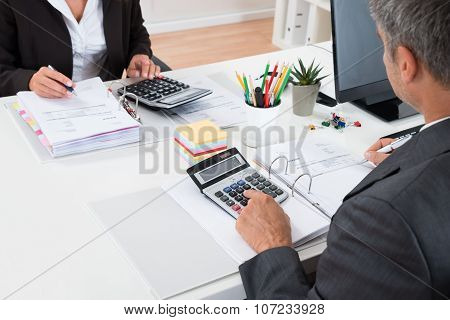 Two Businesspeople Calculating Financial Statement