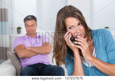 Woman Talking On Mobile Phone In Front Of Her Husband