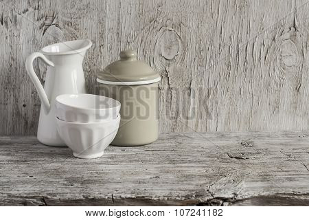 Vintage Crockery - Enamel Jug, Enameled Jar And White Ceramic Bowl On Bright Wooden Surface. Rustic