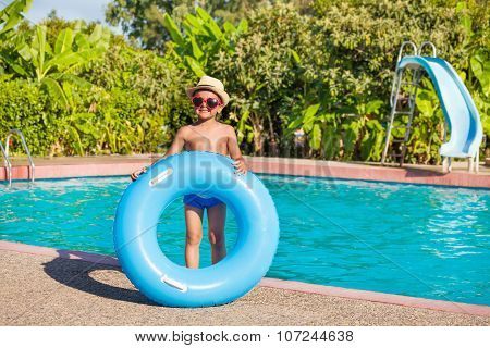 Smiling boy in hat holds blue inflatable ring
