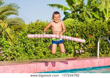 Jumping in pool small boy holding inflatable ring