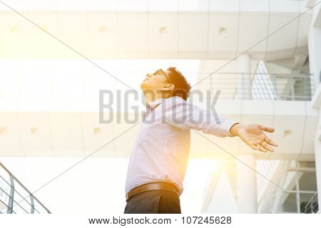 Business freedom concept. Asian businessman arms outstretched enjoying the morning breeze, morning sunlight and modern office as background.