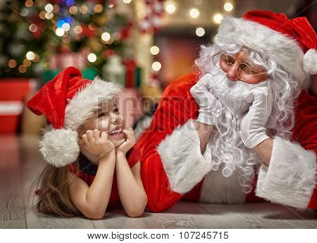 Santa Claus and cute girl getting ready for Christmas.