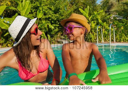 Happy mom and her son wearing sunglasses in pool
