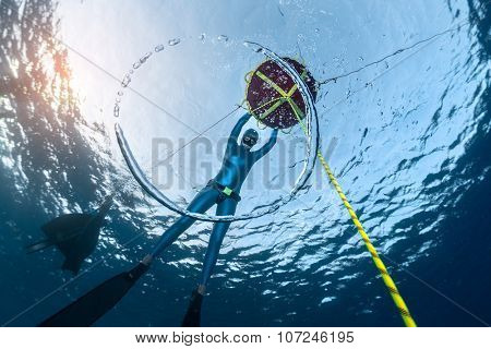 Lady freediver relaxing near the buoy. Ring bubble ascending towards the surface