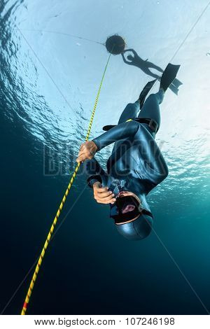 Lady freediver descending along the rope her buddy watching on the surface by the buoy. Free immersion discipline