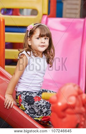 Happy child playing inside on a slide