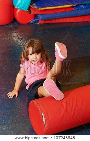Girl doing kids gymnastics in gym of an elementary school
