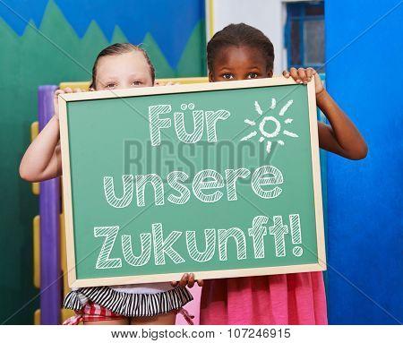 Children holding chalkboard with German slogan