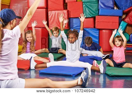 Group of children doing kids gymnastics in gym with nursery teacher